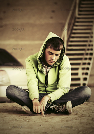 Sad young fashion man sitting on the ground outdoor