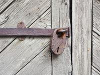 Rostiges Vorhängeschloss an Holztür