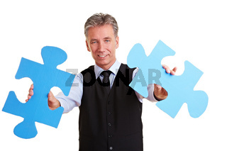 Manager mit zwei Puzzleteilen