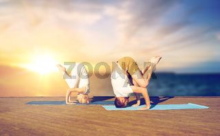 couple doing yoga headstand outdoors