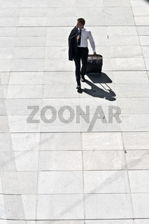 Young Corporate Man With Luggage Walking On Pavement