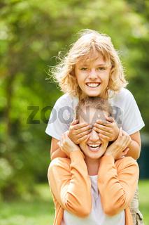 Junge macht Unfug und hält Mutter die Augen zu