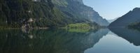 Green meadow and forest mirroring in lake Klontalersee, Switzerland.