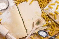 Kochbuch, Kochlöffel, Nudelholz, Nudeln und Mehl auf Holz