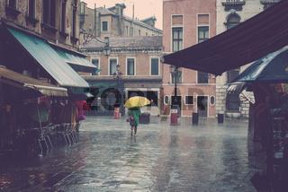 Regnerische Gasse mit einer Frau und gelbem Schirm in Venedig