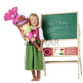 Mädchen mit Schultüte steht am 1. Schultag vor Tafel