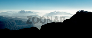 Spectacular view of mountain ranges silhouettes and fog in valleys.