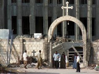 Weisses Kreuz auf einem Torbogen vor einem Kirchenneubau