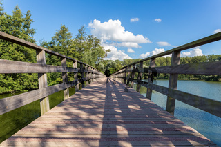 Long wooden bridge over water of pond
