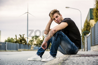 Attractive smiling man sitting by city street