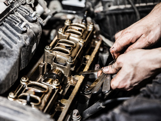 Automobile service worker or garage mechanic repairing auto car engine