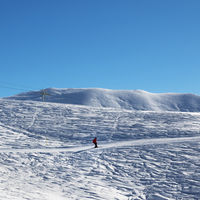 Skier downhill on snowy ski slope at nice sun morning