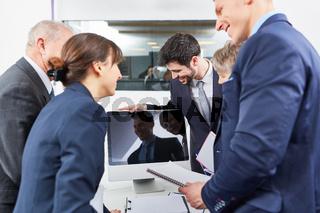 Geschäftsleute stehen um Computer Monitor im Büro