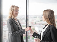 Business woman offering coffee to colleague