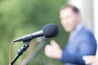 Speaker. Speech. Microphone. News conference.