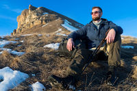 Portrait of tranquil Hipster traveler with beard in sunglasses is sitting on nature.