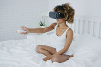 Smiling woman in VR glasses on bed