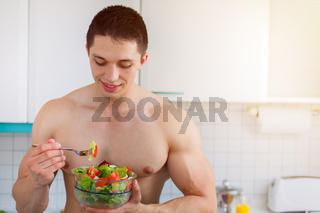 Bodybuilder junger Mann isst essen Salat in der Küche Textfreiraum gesunde Ernährung vegan