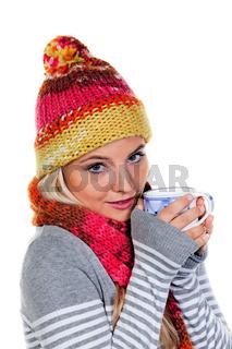 Frau mit Haube wärmt sich mit heißem Tee