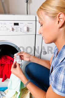 Hausfrau mit Waschmaschine und Wäsche. Waschtag.