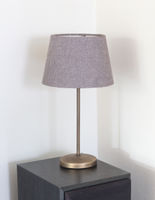 Table lamp standing on a large speaker
