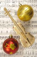 Christbaumkugeln und goldenen Geige liegen auf Musiknoten