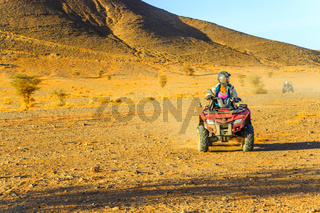 Ait Saoun, Morocco - February 23, 2016: Woman riding quad bike in the desert