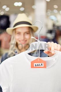 Junge Frau zeigt T-Shirt im Einzelhandel