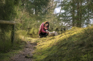 Woman caressing her dog in a fir forest