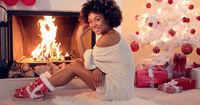 Cute young woman warming herself at the fire