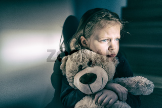 Sad little girl embracing her teddy bear - feels lonely