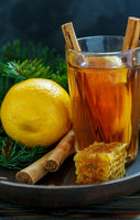 Hot tea with spices and lemon on a wooden tray.