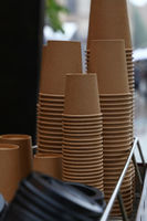 Stack of brown coffee paper cups close up