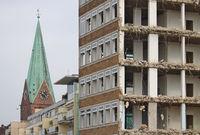 Abgerissenes Gebäude mit Kirchturm im Hintergrund