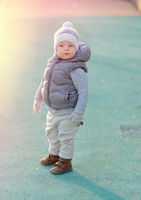 Toddler child in warm vest jacket outdoors. Baby boy at playground during sunset.