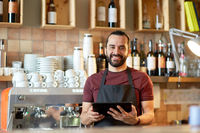 man, barman or waiter with tablet pc at bar