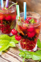 Glasses of refreshing drink flavored with fresh fruit and decorated with cherries covered with dew drops