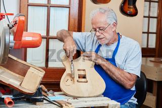 Gitarrenbauer arbeitet am Korpus der Gitarre