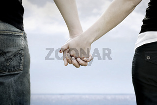 A couple holds hands i