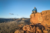 male hiker sitting on a top of sandstone rock formation