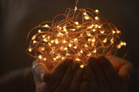 Woman hands holding string of lights in the dark.