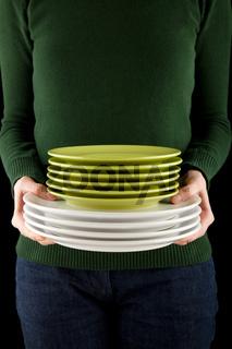 Frau hält Stapel mit grünen und weissen Tellern