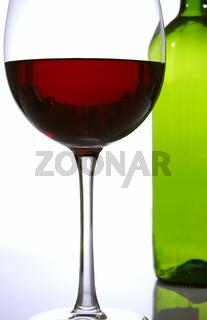 Rotweinglas und leere Weinflasche