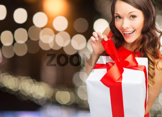 smiling woman in red dress with christmas gift box