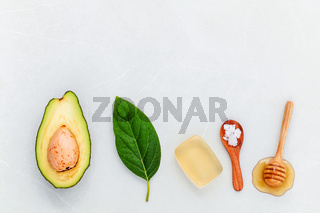 Homemade skin care and body scrubs with fresh  avocado , avocado leaves ,sea salt soap and honey on marble background flat lay and copy space.