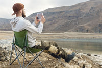 A bearded hipster in a cap sits on a folding chair on the shore of a high mountain lake and takes a photo on a tablet. A bearded blogger is broadcasting from nature. The concept of travel bloggers in nature