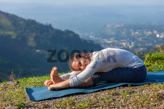 Woman doing yoga asana Paschimottanasana forward bend
