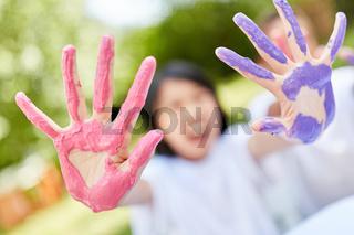 Kind zeigt Hände in lila und rosa Farben