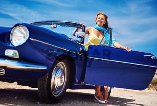 Beautiful happy woman sitting in retro cabriolet car