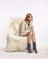 Blonde woman on furry arm-chair with cup of coffee in hands